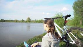 Jovem mulher que monta uma bicicleta atrav?s do parque no fundo de um lago ou de um rio vídeos de arquivo
