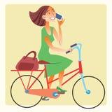 Jovem mulher que monta uma bicicleta e que fala no smartphone Imagens de Stock Royalty Free