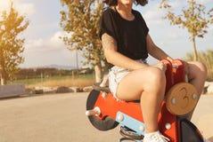 Jovem mulher que monta uma motocicleta do brinquedo no campo de jogos Fotografia de Stock