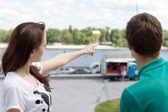 Jovem mulher que mostra o sentido a um turista fotografia de stock royalty free