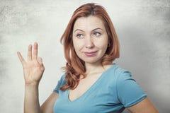 Jovem mulher que mostra o sinal APROVADO Fotografia de Stock