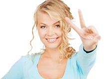 Jovem mulher que mostra o sinal da vitória ou de paz Fotografia de Stock Royalty Free