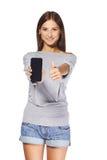 Jovem mulher que mostra o telefone celular móvel Fotos de Stock