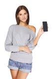 Jovem mulher que mostra o telefone celular móvel Fotografia de Stock