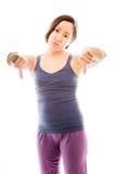 A jovem mulher que mostra os polegares assina para baixo de ambos Fotografia de Stock Royalty Free