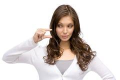 Jovem mulher que mostra a pequena quantidade de algo Fotografia de Stock Royalty Free