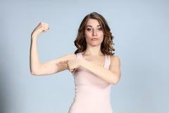A jovem mulher que mostra seus músculos no fundo cinzento fotografia de stock royalty free