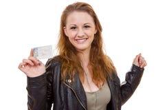 Jovem mulher que mostra sua licença de motorista Imagem de Stock Royalty Free