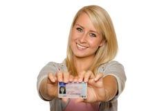 Jovem mulher que mostra sua licença de motorista Fotografia de Stock