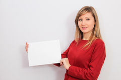 Jovem mulher que mostra uma folha de papel vazia Fotografia de Stock