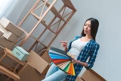 Jovem mulher que move-se para um projeto de planeamento novo da paleta da terra arrendada da posição do lugar imagem de stock
