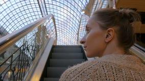 Jovem mulher que move sobre a escada rolante e que olha ao redor na alameda filme