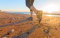 Jovem mulher que movimenta-se na praia da areia ao longo da ressaca do mar em sapatas do nascer do sol perto acima Foto de Stock Royalty Free