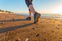 Jovem mulher que movimenta-se na praia da areia ao longo da ressaca do mar em sapatas do nascer do sol perto acima Fotografia de Stock