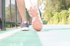 Jovem mulher que movimenta-se no parque na manhã sob o sunlig morno imagens de stock royalty free