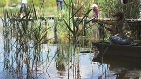 A jovem mulher que o pescador está pescando no lago da floresta, guardando a vara de pesca torce a bobina video estoque