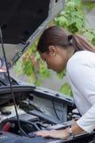 Jovem mulher que olha abaixo do motor de um carro Fotografia de Stock Royalty Free