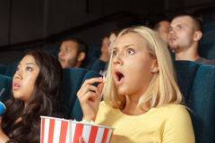 Jovem mulher que olha assustado ao olhar um filme Imagens de Stock