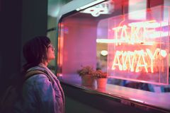 A jovem mulher que olha através do vidro ao lado de um clube com uma janela com luzes de néon leva embora fotografia de stock