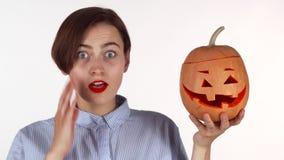 A jovem mulher que olha chocada, levantando com o Dia das Bruxas cinzelou a abóbora vídeos de arquivo