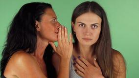 Jovem mulher que olha chocada quando seus amigos que sussurram a ela imagens de stock royalty free