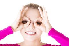Jovem mulher que olha com binocular imaginário Fotos de Stock Royalty Free