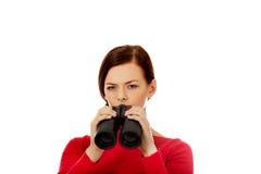 Jovem mulher que olha com um binocular Foto de Stock Royalty Free