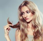 Jovem mulher que olha extremidades rachadas Fotos de Stock Royalty Free