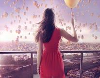 Jovem mulher que olha fixamente em milhares dos balões Imagens de Stock