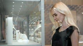 Jovem mulher que olha a mostra e a joia da loja para olhá-la mais perto, modelo de forma louro do estudante bonito dentro Imagens de Stock Royalty Free