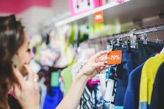 Jovem mulher que olha na etiqueta do disconto na loja da roupa Foto de Stock Royalty Free