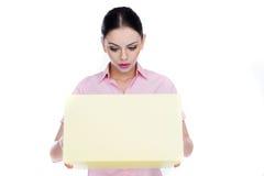 Jovem mulher que olha na perplexidade em uma caixa Fotos de Stock