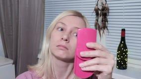 A jovem mulher que olha no espelho e que aplica-se compõe em casa video estoque