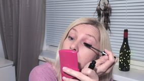A jovem mulher que olha no espelho e que aplica-se compõe em casa filme