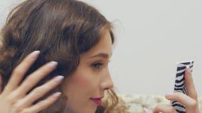 Jovem mulher que olha no espelho e que verifica sua composição vídeos de arquivo
