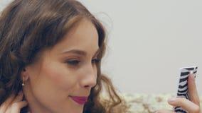 Jovem mulher que olha no espelho e que verifica sua composição video estoque