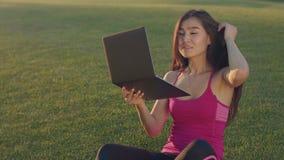 Jovem mulher que olha no portátil como dentro no espelho Mulher asiática que senta-se na grama video estoque