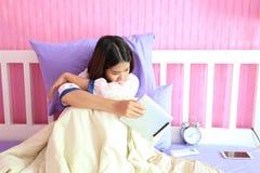 Jovem mulher que olha o dispositivo esperto da tabuleta com o sentimento triste e fotografia de stock royalty free