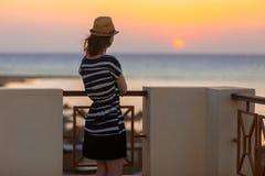 Jovem mulher que olha o nascer do sol fotografia de stock royalty free
