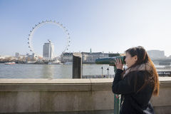 Jovem mulher que olha o olho de Londres através do visor estacionário em Londres, Inglaterra, Reino Unido Imagem de Stock Royalty Free
