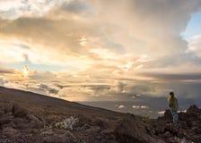 A jovem mulher que olha o sol ajustou-se sobre a cratera de Haleakala Fotografia de Stock