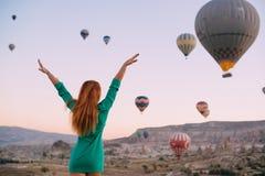 Jovem mulher que olha os braços dos balões estendidos foto de stock royalty free