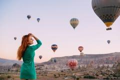 Jovem mulher que olha os braços dos balões estendidos fotos de stock royalty free