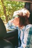 Jovem mulher que olha a paisagem através do carro da janela Fotografia de Stock