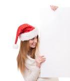 Jovem mulher que olha para fora a placa branca Imagens de Stock Royalty Free