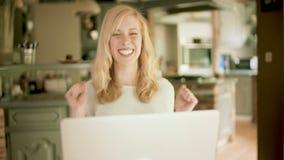 A jovem mulher que olha seu portátil excitou muito video estoque