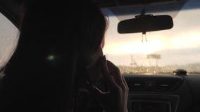 A jovem mulher que olha a seu smartphone ao conduzir o carro, sol brilha atrav?s da janela dianteira Motorista da menina para usa filme