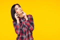 Jovem mulher que olha surpreendida, falando no telefone celular, conversação agradável de condução no fundo amarelo fotos de stock