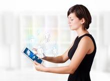 Jovem mulher que olha a tabuleta moderna com ícones sociais Fotografia de Stock Royalty Free