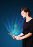 Jovem mulher que olha a tabuleta moderna com luzes abstratas Fotos de Stock Royalty Free